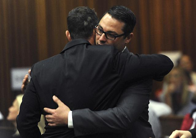 Oscar Pistorius, and his brother Carl, right, embrace inside court on the fourth day of his trial at the high court in Pretoria, South Africa, Thursday, March 6, 2014. Pistorius is charged with murder for the shooting death of his girlfriend, Reeva Steenkamp, on Valentines Day in 2013. (AP Photo/Werner Beukes, Pool)