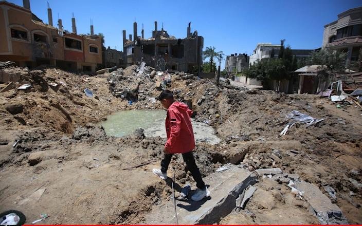 A Palestinian looks for his belongings in the rubble of buildings destroyed by Israeli airstrikes in Gaza City - Anadolu