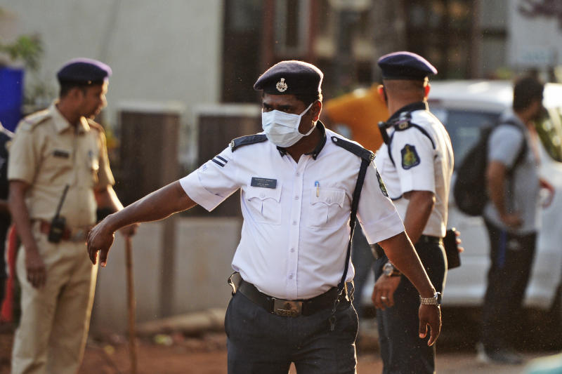 Security personnel wearing facemasks amid concerns over the spread of the COVID-19 novel coronavirus, stand guard outside the Jawaharlal Nehru football stadium. Source: Getty Images