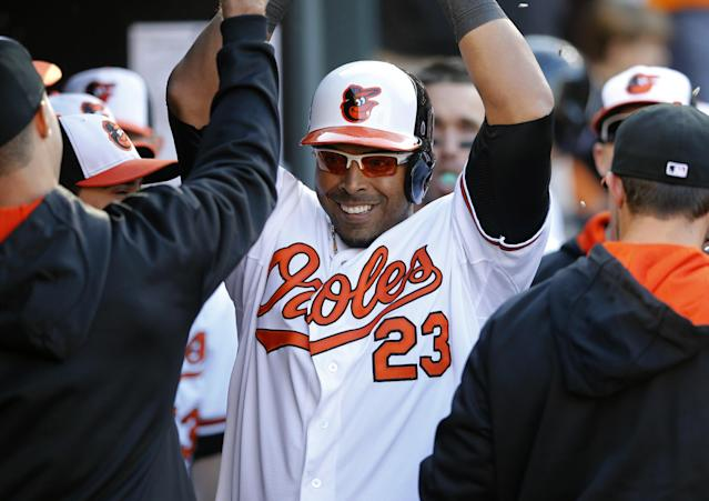 Baltimore Orioles' Nelson Cruz high-fives teammates in the dugout after hitting a solo home run in the seventh inning of an opening day baseball game against the Boston Red Sox, Monday, March 31, 2014, in Baltimore. Baltimore won 2-1. (AP Photo/Patrick Semansky)