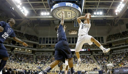 Pittsburgh's James Robinson (0) shoots over Villanova's Tony Chennault, center, in the first half of an NCAA college basketball game on Sunday, March 3, 2013, in Pittsburgh. (AP Photo/Keith Srakocic)