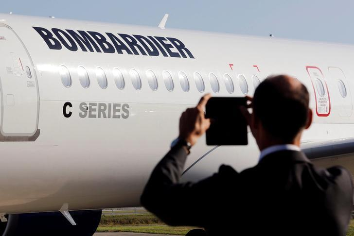 A man takes a picture of a Bombardier CSeries aircraft during a news conference to announce a partnership between Airbus and Bombardier on the C Series aircraft programme, in Colomiers