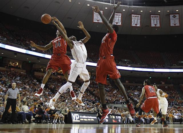Texas' Isaiah Taylor (1) is blocked from behind by Texas Tech's Robert Turner (14) during the first half of an NCAA college basketball game, Saturday, Jan. 11, 2014, in Austin, Texas. Texas Tech's Kader Tapsoba, right, assists on the play. (AP Photo/Eric Gay)