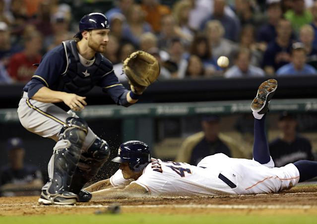 Houston Astros' Justin Maxwell, right, slides safely into home plate to score as Milwaukee Brewers' Jonathan Lucroy, left, reaches for the throw during the fourth inning of a baseball game Tuesday, June 18, 2013, in Houston. Maxwell scored on a bunt by Marwin Gonzalez. (AP Photo/David J. Phillip)