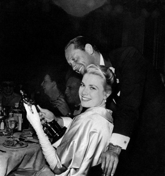 <p>Kelly smiles as William Holden admires her Academy Award. Kelly and Holden costarred in <em>The</em> <em>Country Girl</em> together.</p>
