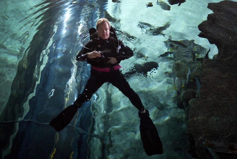 """In this photo taken on Saturday, July 28, 2012, American journalist and diving instructor Steven Schwankert in diving suit swims inside the Blue Zoo aquarium in Beijing, China. A lifelong scuba diving obsession led Schwankert to the tale of the HMS Poseidon and the startling discovery that the British submarine, which sank off the northeastern coast of China in the 1930s, had been raised by the Chinese in 1972. That revelation lies at the heart of Schwankert's upcoming book, """"The Real Poseidon Adventure: China's Secret Salvage of Britain's Lost Submarine"""" and an accompanying documentary film chronicling his search for answers about what became of the sunken vessel. (AP Photo/Andy Wong)"""