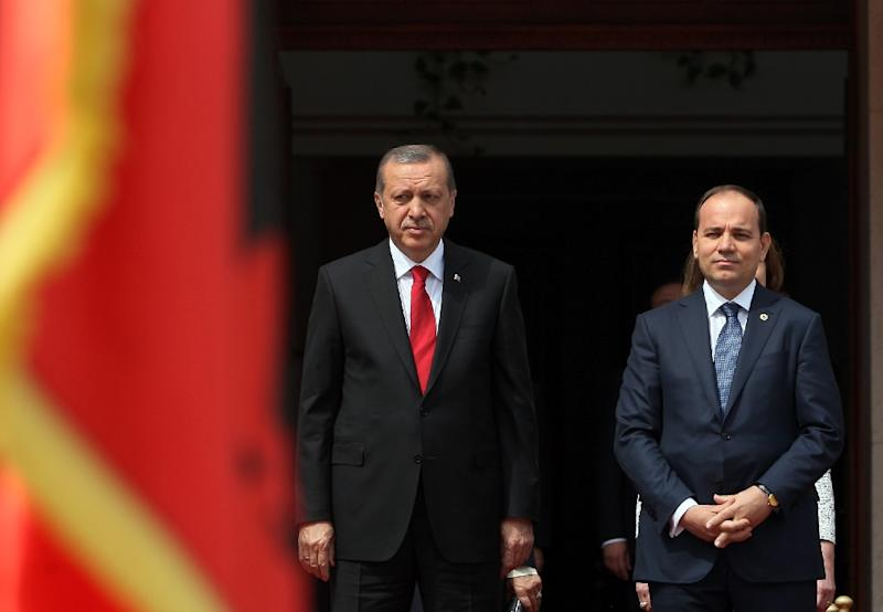 Albanian President Bujar Nishani (R) and Turkish counterpart Recep Tayyip Erdogan listen to their respective national anthems during a welcoming ceremony before their meeting in Tirana on May 13, 2015
