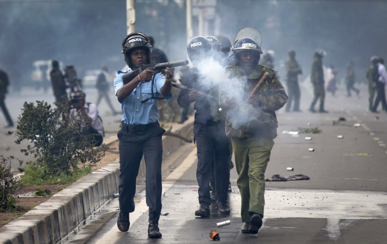 Riot police fire tear gas toward demonstrators as they flee during a protest in downtown Nairobi, Kenya, May 16, 2016. Kenyan police have tear-gassed and beaten opposition supporters during a protest demanding the disbandment of the electoral authority over alleged bias and corruption. (AP Photo/Ben Curtis)