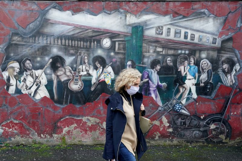 FILE PHOTO: A woman walks past a wall mural during the resurging coronavirus ouitbreak in Galway, Ireland