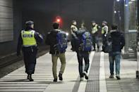 A police officer escorts migrants from a train at Hyllie station outside Malmo, Sweden, in this November 19, 2015 file photo. Thousands of Iraqi refugees who arrived in Finland last year have decided to cancel their asylum applications and to return home voluntarily, citing family issues and disappointment with life in the frosty Nordic country. REUTERS/Johan Nilsson/TT NEWS AGENCY/Files