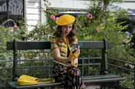 <p>Emily wears a matching yellow beret, bag, and gloves with a printed dress and plaid jacket. </p>