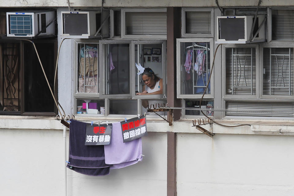 """A resident uses a mobile phone to film protesters marching through the street to continue protesting against the extradition bill, Sunday, June 16, 2019, in Hong Kong. Hong Kong residents Sunday continued their massive protest over an unpopular extradition bill that has highlighted the territory's apprehension about relations with mainland China, a week after the crisis brought as many as 1 million into the streets. The posters read """"Students not violence, seeking responsibility on gun shooting, withdraw the charges"""". (AP Photo/Kin Cheung)"""