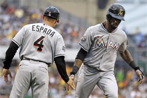 Miami Marlins' Jose Reyes, right, rounds third to greetings from coach Joe Espada (4) after hitting a solo home run off Pittsburgh Pirates pitcher Kevin Correia during the first inning of a baseball game in Pittsburgh on Friday, July 20, 2012. (AP Photo/Gene J. Puskar)