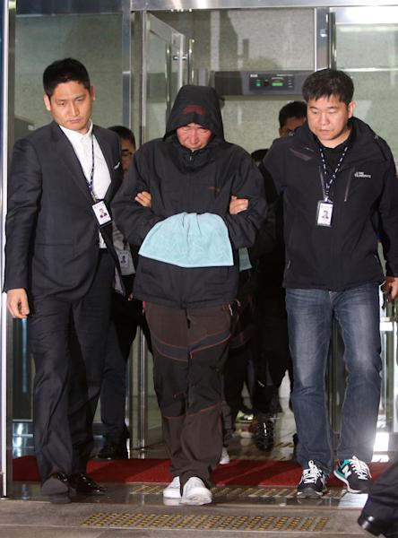 Lee Joon-seok, center, the captain of the sunken ferry Sewol in the water off the southern coast, leaves a court which issued his arrest warrant in Mokpo, south of Seoul, South Korea, Saturday, April 19, 2014. The investigation into South Korea's ferry disaster focused on the sharp turn it took just before it began listing and on the possibility that a quicker evacuation order by the captain could have saved lives, officials said Friday, as rescuers struggled to find some 270 people still missing and feared dead. (AP Photo/Yonhap) KOREA OUT