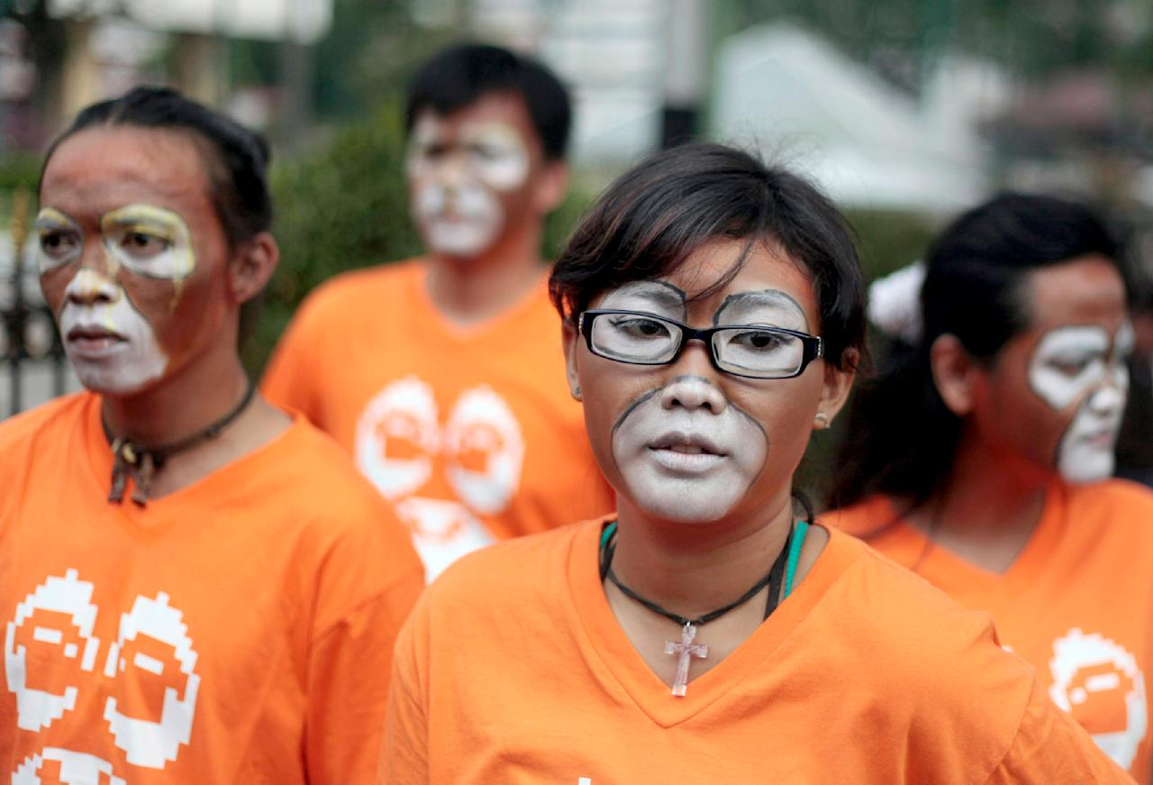 Activists of the Center for Orangutan Protection have their face painted as orangutan during a protest demanding improvement of orangutans' welfare by the government at Jakarta's Ragunan Zoo outside the governor's office in Jakarta, Indonesia, Thursday, Aug. 4, 2011. The activists said that the zoo did not provide decent living environment for their orangutans causing them to fall into depression. Orangutan populations in Indonesia's Borneo and Sumatra islands are facing severe threats from habitat loss, illegal logging, fires and poaching. (AP Photo/Dita Alangkara)
