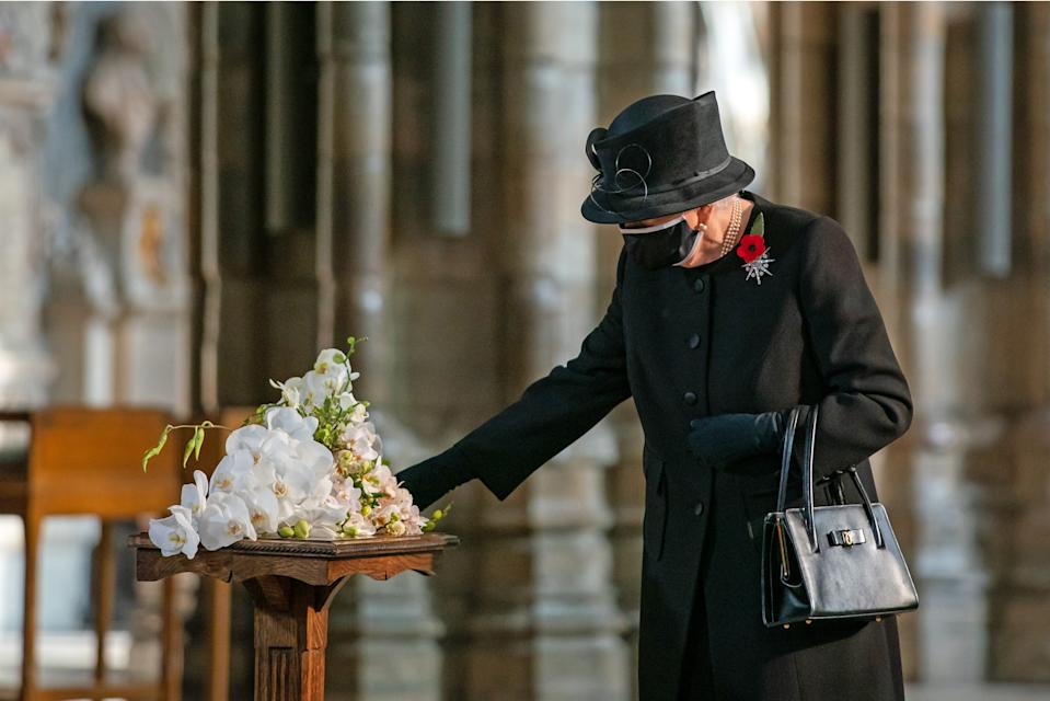 LONDON, ENGLAND - NOVEMBER 04: Queen Elizabeth II inspects a bouquet of flowers placed on her behalf at the grave of the Unknown Warrior by her Equerry, Lieutenant Colonel Nana Kofi Twumasi-Ankrah, during a ceremony in Westminster Abbey to mark the centenary of the burial of the Unknown Warrior on November 4, 2020. The grave of the Unknown Warrior is the final resting place of an unidentified British serviceman who died on the battlefields during the First World War and whose body was brought from Northern France and buried at Westminster Abbey on 11th November 1920. (Photo by Aaron Chown - WPA Pool/Getty Images)