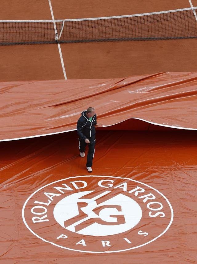 A stadium employee removes the protective canvas on center court after rain delayed the play for the first round match of the French Open tennis tournament at the Roland Garros stadium, in Paris, France, Monday, May 26, 2014. (AP Photo/Michel Euler)