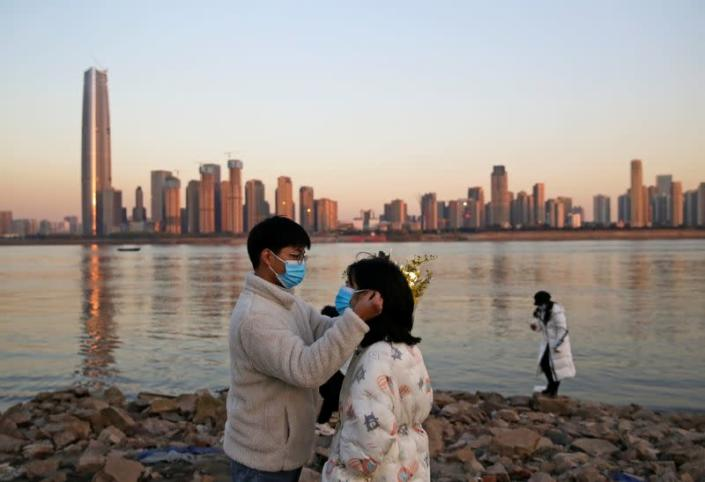 Man puts on a mask for a woman by a river on New Year's Eve in Wuhan