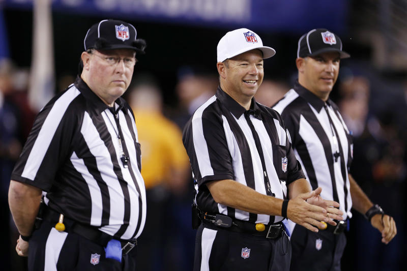 Referee Jim Core, center, gestures alongside other game officials before an NFL football game between the New York Giants and the Dallas Cowboys, Wednesday, Sept. 5, 2012, in East Rutherford, N.J. (AP Photo/Julio Cortez)
