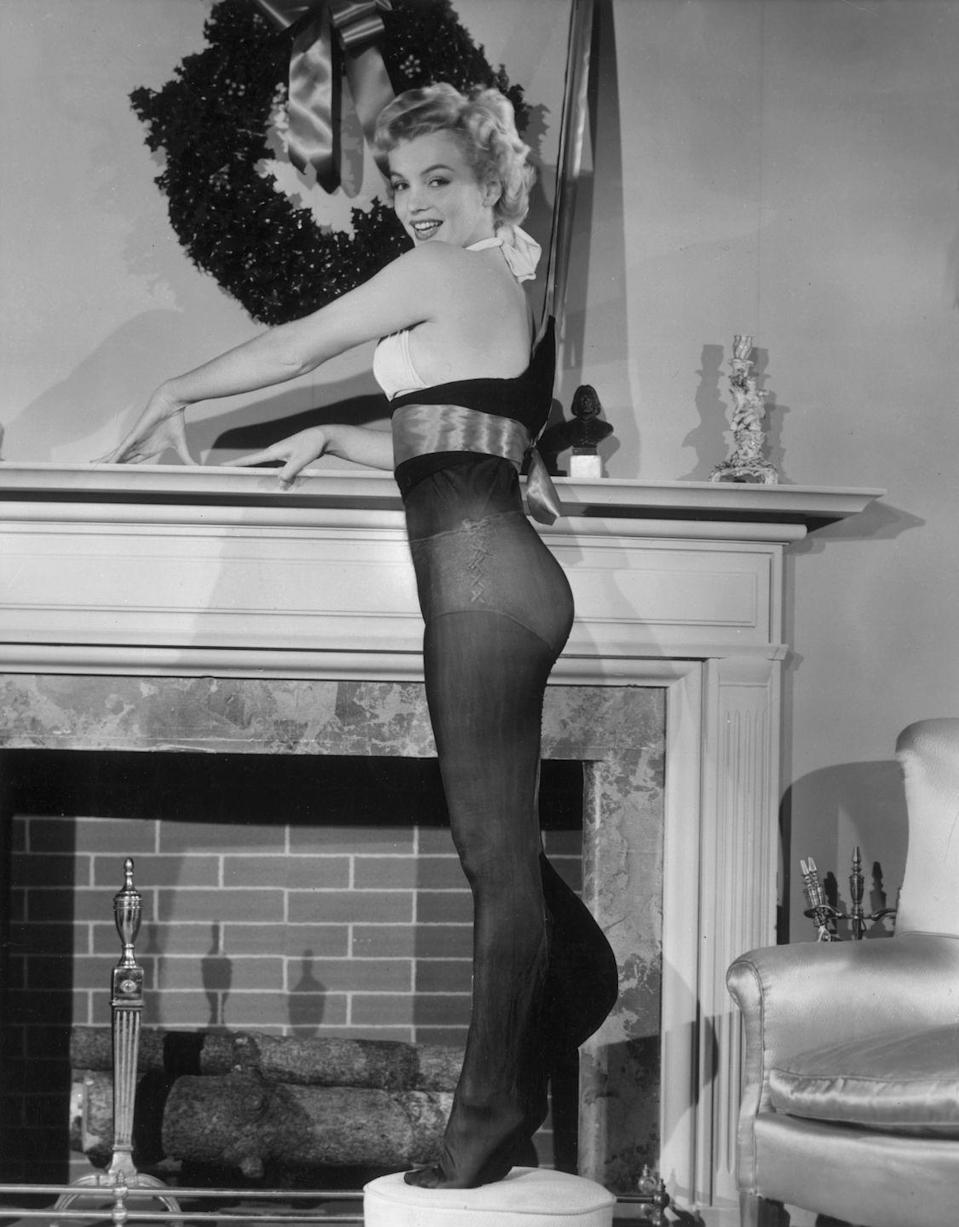 <p>The blonde bombshell models next to a fireplace and holiday wreath in 1951.</p>