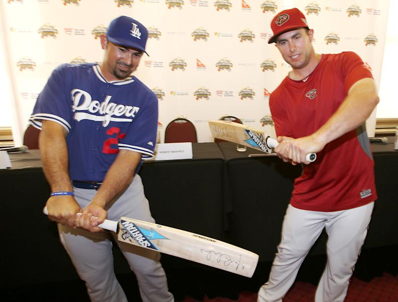 The Los Angeles Dodgers' Adrian Gonzalez, left, and The Arizona Diamondbacks' Paul Goldschmidt try swinging cricket bats at the Sydney Cricket Ground in Sydney, Tuesday, March 18, 2014. The MLB season-opening two-game series between the Los Angeles Dodgers and Arizona Diamondbacks in Sydney will be played this weekend. (AP Photo/Rick Rycroft)