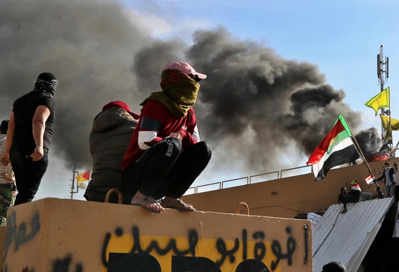 Pro-Iranian militiamen and their supporters set a fire during a sit-in in front of the U.S. embassy in Baghdad, Iraq, Wednesday, Jan. 1, 2020. U.S. troops have fired tear gas to disperse hundreds of pro-Iran militiamen and other protesters who were gathered for a second day outside the American Embassy compound in Baghdad. (AP Photo/Khalid Mohammed)