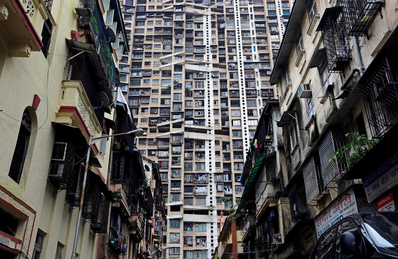 A high-rise residential tower is pictured behind old residential buildings in Mumbai, India July 24, 2017. REUTERS/Danish Siddiqui     TPX IMAGES OF THE DAY