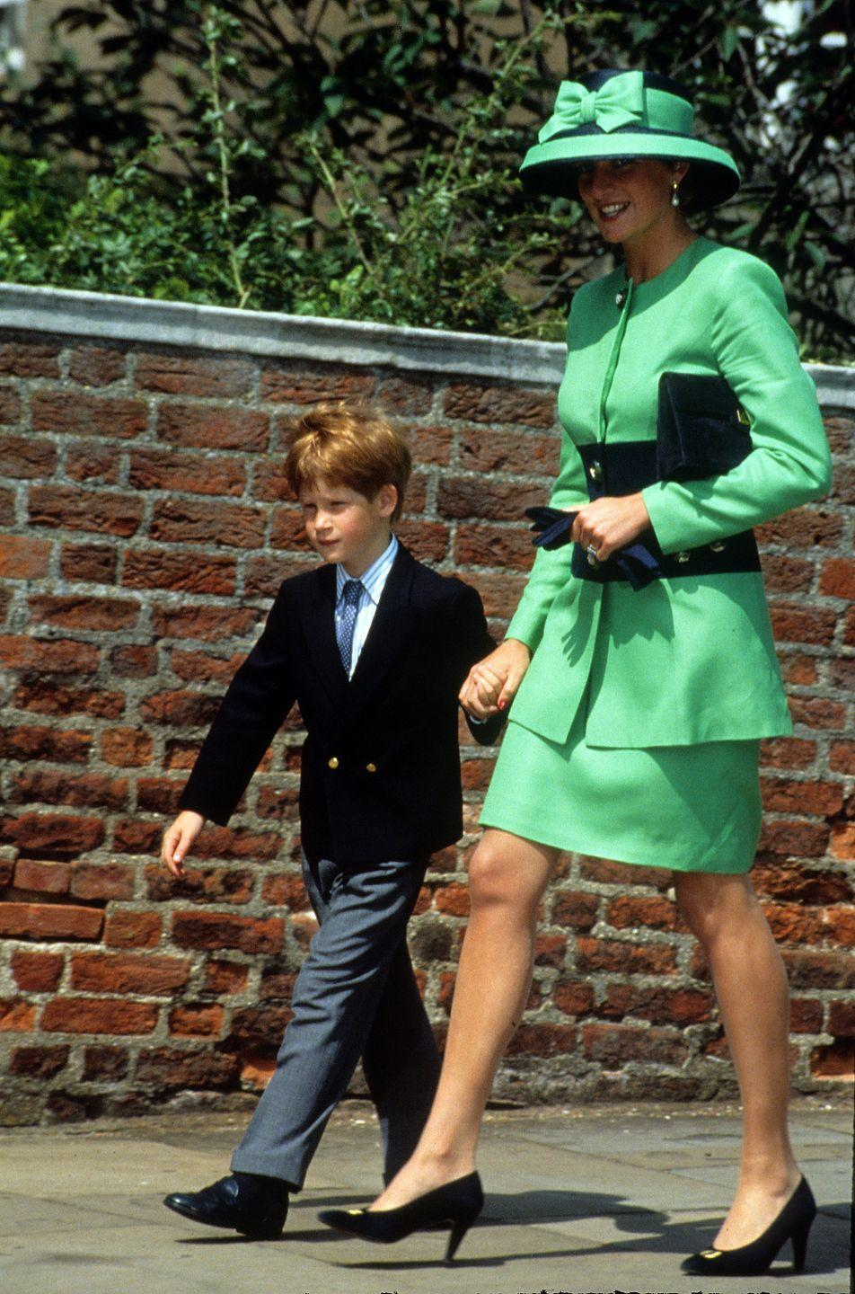 """<p>Princess Diana and Prince Harry walk to <a href=""""https://www.townandcountrymag.com/society/tradition/a14392230/st-george-chapel-windsor-castle-meghan-markle-prince-harry-wedding-venue/"""" rel=""""nofollow noopener"""" target=""""_blank"""" data-ylk=""""slk:St. George's Chapel"""" class=""""link rapid-noclick-resp"""">St. George's Chapel</a> for the wedding of Lady Helen Windsor to Tim Taylor. Diana is decked out in green from head to toe for the occasion. </p>"""
