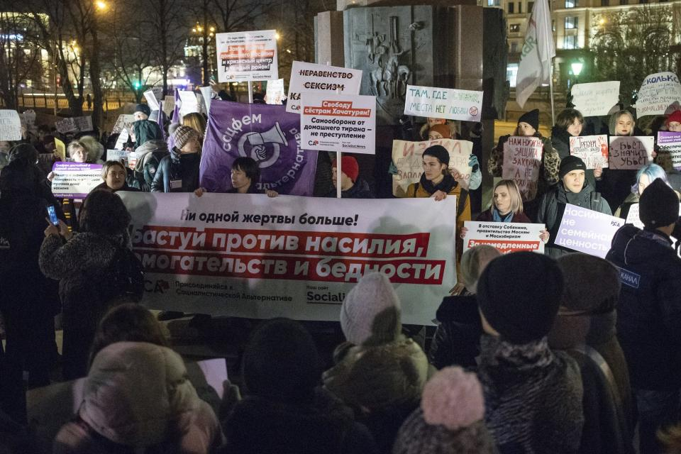 FILE - In this Nov. 25, 2019, file photo, people hold banners against domestic violence as they attend a rally in Moscow's downtown, Russia. Few reliable official statistics are kept on violence against women in Russia, but it is clearly a national problem. Police routinely turn a blind eye to domestic abuse, and restraining orders don't exist, leaving victims without a key protection. (AP Photo/Pavel Golovkin, File)