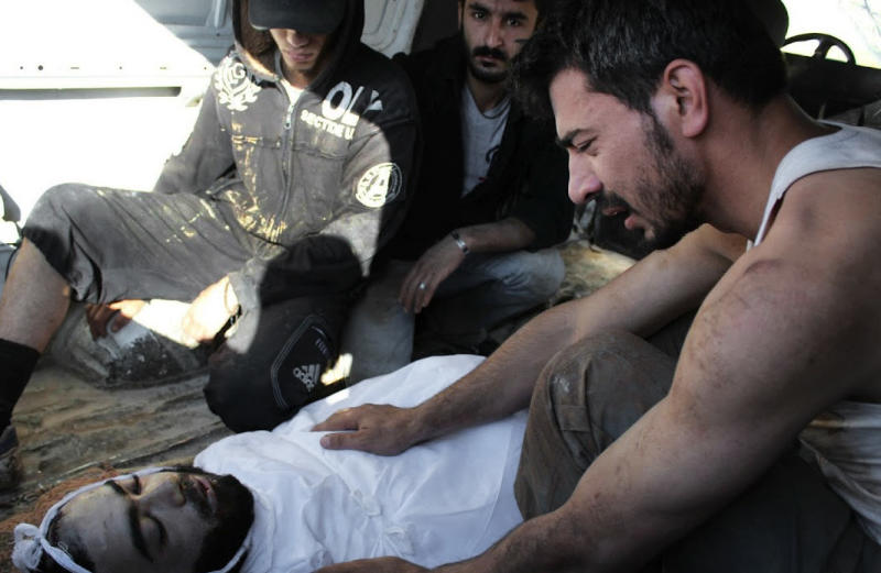 In this citizen journalism image provided by Shaam News Network SNN, taken on Saturday, July 14, 2012, a Syrian man mourns over the body of a man killed, in Homs, Syria. On Sunday Syria denied U.N. claims that government forces used heavy weapons during a military operation that left scores dead. (AP Photo/Shaam News Network, SNN)THE ASSOCIATED PRESS IS UNABLE TO INDEPENDENTLY VERIFY THE AUTHENTICITY, CONTENT, LOCATION OR DATE OF THIS CITIZEN JOURNALIST IMAGE