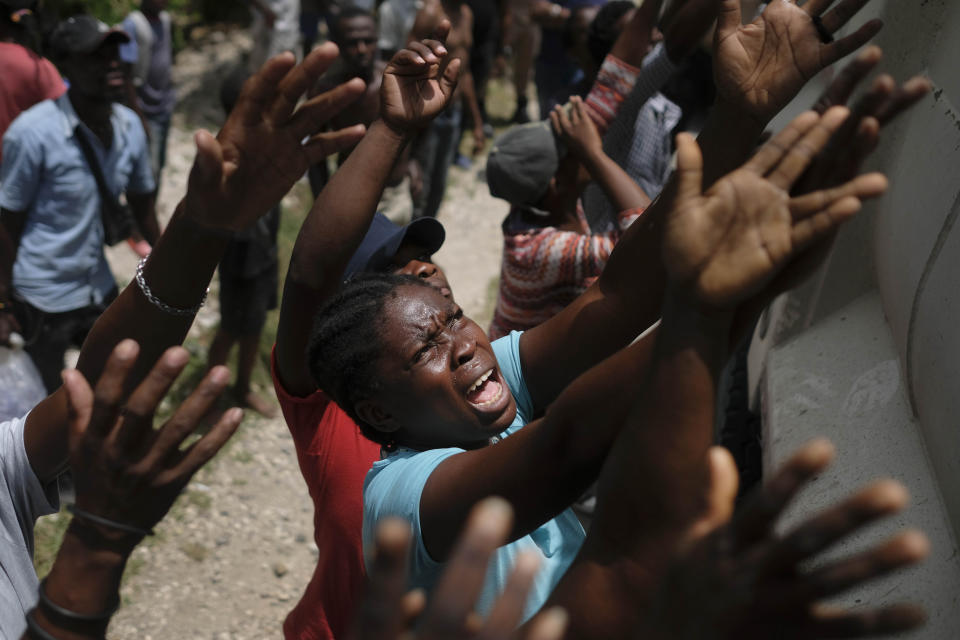 In this Aug. 22, 2021 file photo, earthquake victims reach for water being handed out during a food distribution in the Picot neighborhood in Les Cayes, Haiti, eight days after a 7.2 magnitude earthquake hit the area. (Matias Delacroix/ AP File)