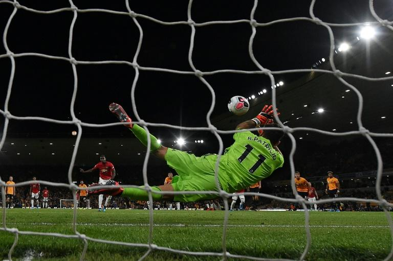 Wolves goalkeeper Rui Patricio (R) saves a penalty from Manchester United's Paul Pogba forcing United to settle for a 1-1 draw