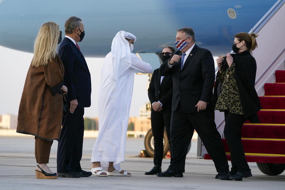 Secretary of State Mike Pompeo, second from right, elbow-bumps Shihab al-Faheem, chief of protocol with the United Arab Emirates' Ministry of Foreign Affairs, as he and his wife Susan, right, step off a plane at Al Bateen Executive Airport in Abu Dhabi, United Arab Emirates, Friday, Nov. 20, 2020. Also pictured are Terry Rakolta, left, and her husband, U.S. Ambassador to the UAE John Rakolta. (AP Photo/Patrick Semansky, Pool)