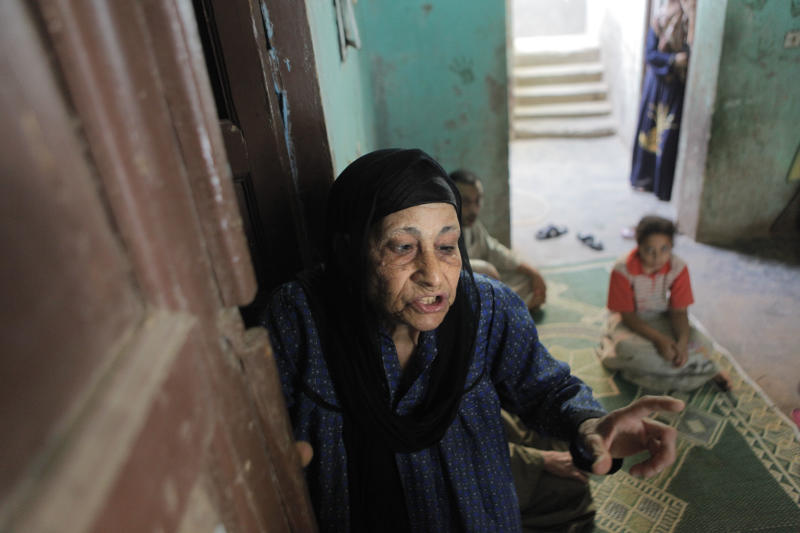 In this Thursday, Aug. 2, 2012 photograph, Egyptian Christian Sameeha Wehba, 70, the only Christian who remains at Dahshour village, is hosted by Muslim family of Mahmoud Abou Abdel Karim, at Dahshour village, about 40 kilometers (25 miles) south of Cairo, Egypt, a day after a sectarian violence erupted in the village following the death of a Muslim man, prompting most the local Christians to flee, church and security officials said. (AP Photo/Amr Nabil)