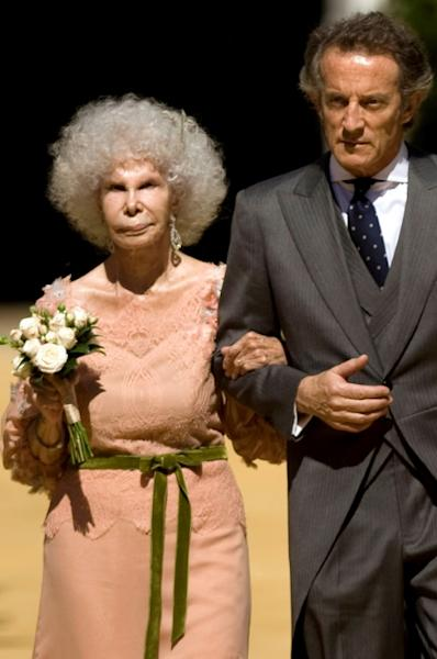Spain's Duchess of Alba, Maria del Rosario Cayetana Fitz-James-Stuart and her husband Alfonso Diez walk towards photographers after their wedding ceremony at the Palacio de las Duenas in Sevilla on October 5, 2011