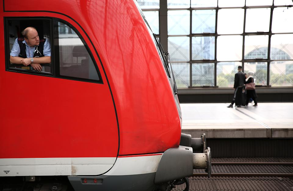 """BERLIN, GERMANY - AUGUST 10: A regional (RB) train driver looks out of his window at Berlin's main train station, or Hauptbahnhof, on August 10, 2021 in Berlin, Germany. Ninety-five percent of the Gewerkschaft Deutscher Lokomotivführer (GDL) train drivers' union members voted in favor of a strike affecting cargo and passenger trains expected to last 48 hours, as they call for a 3.2% salary increase and a one-time """"coronavirus bonus"""" of 600 euros (703 USD). (Photo by Adam Berry/Getty Images)"""