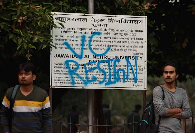 Students stand next to a notice board that has been sprayed with the slogan VC RESIGN, demanding the resignation of the Vice-Chancellor M Jagadesh Kumar, as part of the protests against the administrations move to hike the hostel fee, at JNU, on November 15, 2019. JNUSU said it has received an overwhelming support from more than 150 universities and institutes across the world in its battle against the hostel fee hike. (Photo: Hindustan Times via Getty Images)