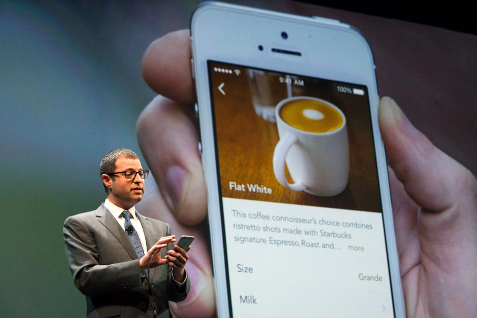 Starbucks Chief Digital Officer Adam Brotman demonstrates how to order a drink using the new mobile ordering system during the company's annual shareholder's meeting in Seattle, Washington March 18, 2015. Starbucks Corp will begin offering delivery in New York City and Seattle later this year, when it also plans to expand mobile order and pay services across the United States.  REUTERS/David Ryder  (UNITED STATES - Tags: BUSINESS)