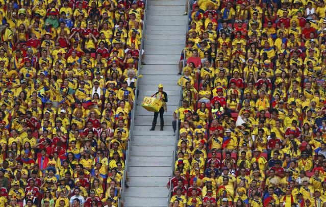 A vendor walks down the stairs as fans watch the 2014 World Cup Group C soccer match between Ivory Coast and Colombia at the Brasilia national stadium in Brasilia June 19, 2014. REUTERS/Eddie Keogh (BRAZIL - Tags: SOCCER SPORT WORLD CUP TPX IMAGES OF THE DAY)