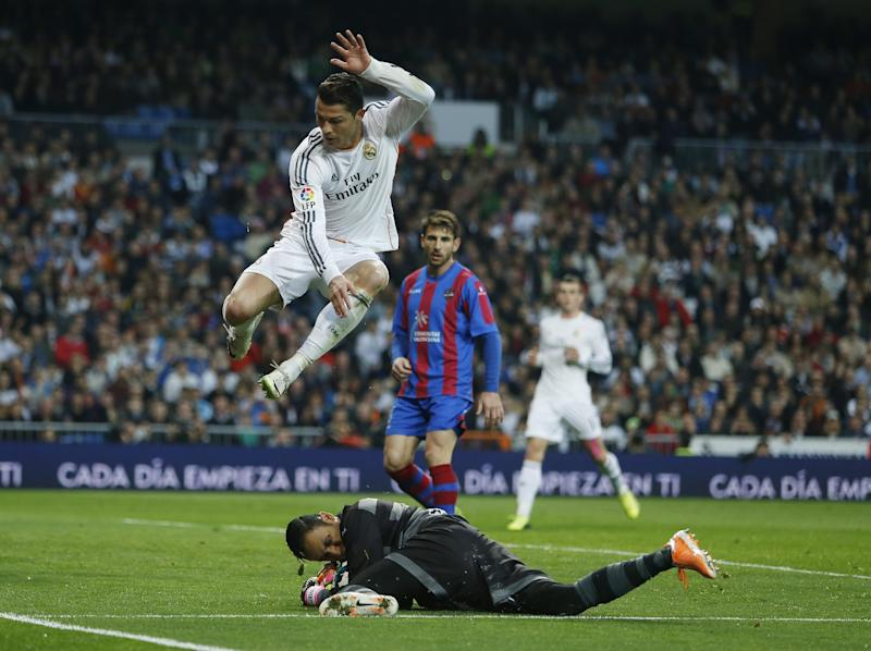 Real's Cristiano Ronaldo, top, in action Levante's goalkeeper Keylor Navas, bottom, during a Spanish La Liga soccer match between Real Madrid and Levante at the Santiago Bernabeu stadium in Madrid, Spain, Sunday, March 9, 2014. (AP Photo/Andres Kudacki)