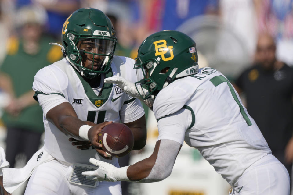 Baylor quarterback Gerry Bohanon (11) hands the ball to running back Abram Smith (7) during the second half of an NCAA college football game against Kansas in Lawrence, Kan., Saturday, Sept. 18 2021. Baylor defeated Kansas 45-7. (AP Photo/Orlin Wagner)