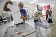 Voters cast their ballots at a polling station during the Parliamentary elections in Krymsk, Krasnodar region, Russia, Sunday, Sept. 19, 2021. The election is widely seen as an important part of President Vladimir Putin's efforts to cement his grip on power ahead of the 2024 presidential polls, in which control of the State Duma, or parliament, will be key. (AP Photo)