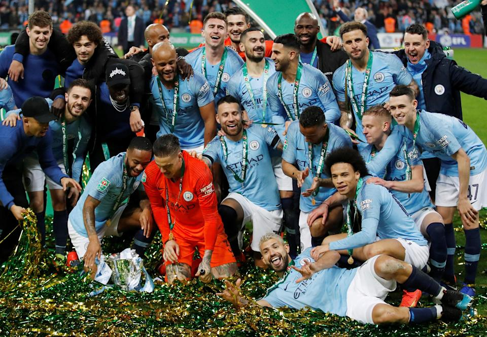 Manchester City players pose with the Carabao Cup trophy after winning the final. (PHOTO: Reuters/Carl Recine)