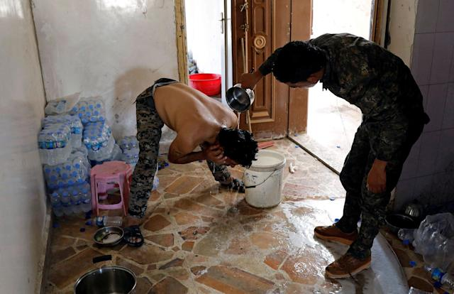 <p>A member of the Syrian Democratic Forces helps his comrade wash his hair at their position at the frontline in Raqqa, Syria, Oct. 7, 2017. (Photo: Erik De Castro/Reuters) </p>