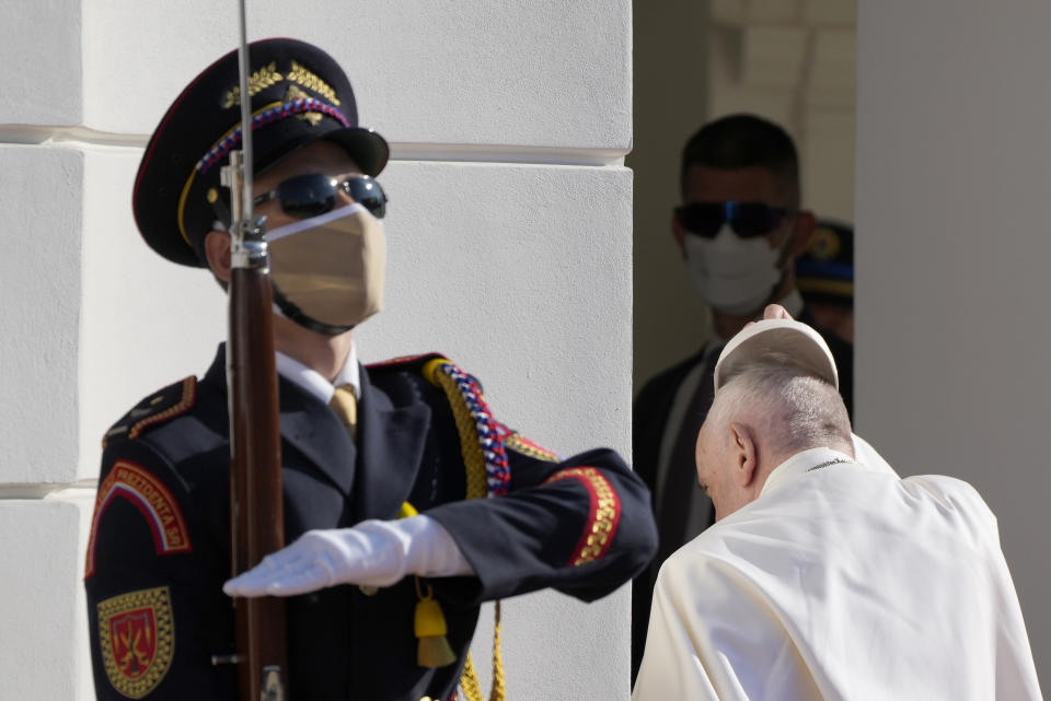 Pope Francis takes off his cap as he enters the presidential palace in Bratislava, Slovakia, Monday, Sept. 13, 2021. Francis is on a four-day visit to Central Europe, in Hungary and Slovakia, in his first big international outing since undergoing intestinal surgery in July. (AP Photo/Gregorio Borgia)