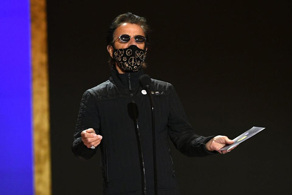 <p>Wearing a black outfit with a matching face mask featuring gold peace signs.</p>