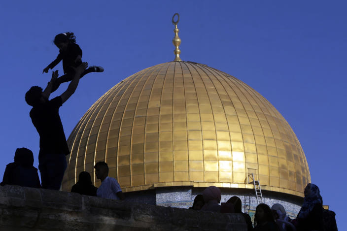 A girl is tossed into the air as people gather for Eid al-Fitr prayers at the Dome of the Rock Mosque in the Al-Aqsa Mosque compound in the Old City ofJerusalem, Thursday, May 13, 2021. Eid al-Fitr, festival of breaking of the fast, marks the end of the holy month of Ramadan. (AP Photo/Mahmoud Illean)