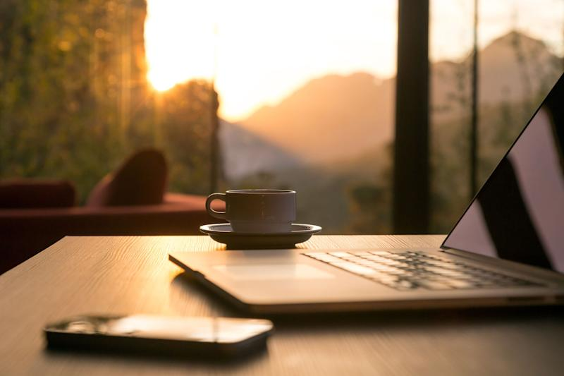 A laptop, smartphone, and cup of coffee sitting on a table. A window with sunshine shining through is in the background.