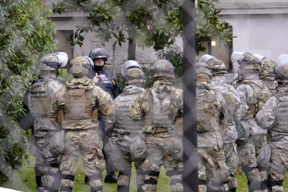 A Washington State Patrol trooper talks with members of the Washington National Guard inside a fence surrounding the Capitol in anticipation of protests Monday, Jan. 11, 2021, in Olympia, Wash. State capitols across the country are under heightened security after the siege of the U.S. Capitol last week. (AP Photo/Ted S. Warren)