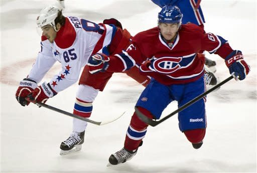Washington Capitals' Mathieu Perreault , left,and Montreal Canadiens' Raphael Diaz collide during first period NHL hockey action, Saturday, Feb. 4, 2012 in Montreal. (AP Photo/The Canadian Press, Paul Chiasson)